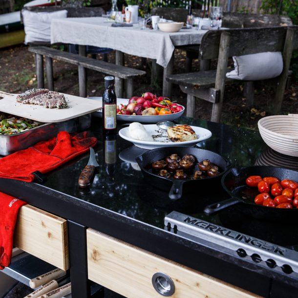 Merklinger Holzbackofen Grill Pizzaofen Brotbackofen mobiler Seitentisch aus Granit angerichtet mit verschiedenen Speisen